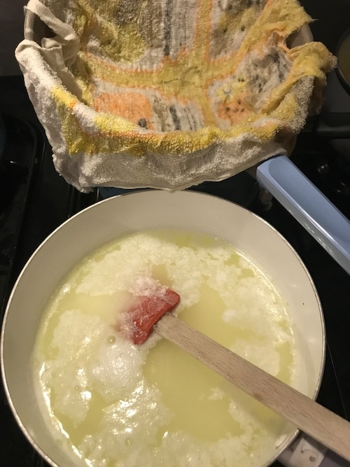 Ladle the curds into the strainer with the cloth in it