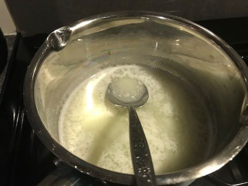 Photo of cheesy bits in a pan that form if you use whey to make milky gummies for dogs